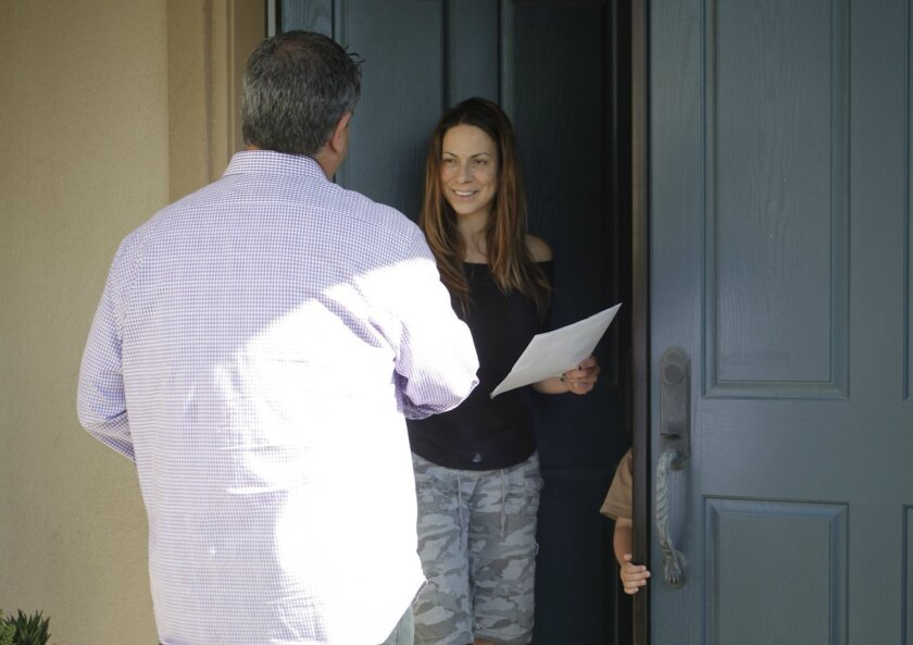 San Diego real estate agent Leon Alchalel walks a Carmel Valley neighborhood, hoping to get some bites and leads and make connections. He says it's a numbers game and can be time-consuming but it's worth it.