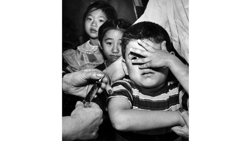 Feb. 25, 1957: Manuel Reyes, 7, peeks apprehensively between fingers at needle just before getting h