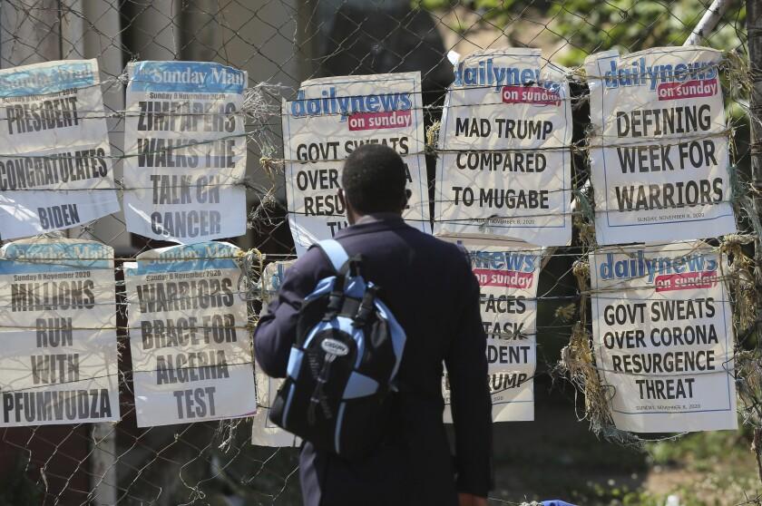 A man reads newspaper headlines on a street of Harare, Sunday, Nov. 8, 2020. Zimbabwean President Emmerson Mnangagawa has sent a congratulatory message to U.S. President-elect Joe Biden who won the U.S. presidential election, beating incumbent Donald Trump. (AP Photo/Tsvangirayi Mukwazhi)