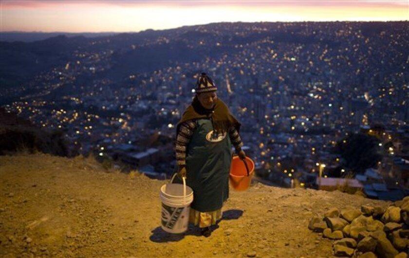 En esta imagen, tomada el 16 de noviembre de 2016, una mujer carga con dos baldes vacíos mientras espera la llegada de un camión cisterna con agua a cerca de su vecindario en La Paz, Bolivia. El presidente del país, Evo Morales, pidió perdón a los residentes de La Paz por la escasez de agua provocada por la peor sequía en 25 años y reconoció que no hay una solución inmediata al problema.