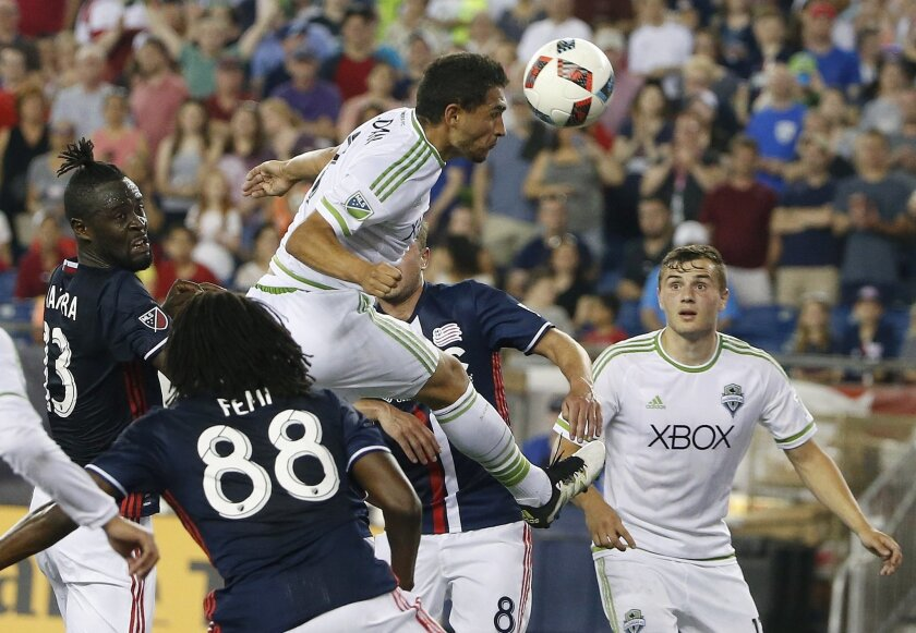 Seattle Sounders's Cristian Roldan, top, heads the ball in front of New England Revolution's Femi Hollinger-Janzen (88) during the second half of an MLS soccer game, Saturday, May 28, 2016, in Foxborough, Mass. The Revolution won 2-1. (AP Photo/Michael Dwyer)