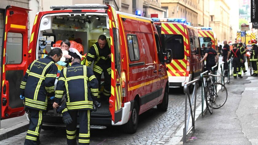 Emergency workers attend to an injured person after a blast on a street in Lyon, France, on May 24.