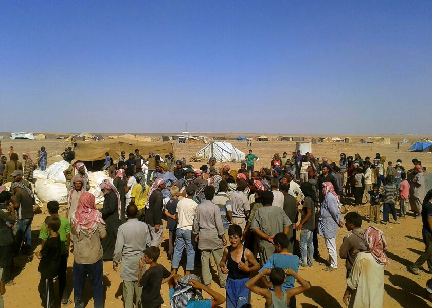 FILE - In this Aug. 4, 2016 file photo, people gather to take basic food stuffs and other aid from community leaders charged with distributing equitably the supplies to the 64,000-person refugee camp called Ruqban on the Jordan-Syria border. Over the last two days, members of the UN Security Council have been haggling over cross-border aid delivery to Syria, with Russia, a major ally of the Syria government, working to reduce the delivery of U.N. humanitarian aid to Syria's last rebel-held northwest down from two crossings to just one. A final vote is expected Friday, July 10, 2020 as western countries push on a new resolution to keep the two crossings open for six months, instead of a year. (AP Photo, File)