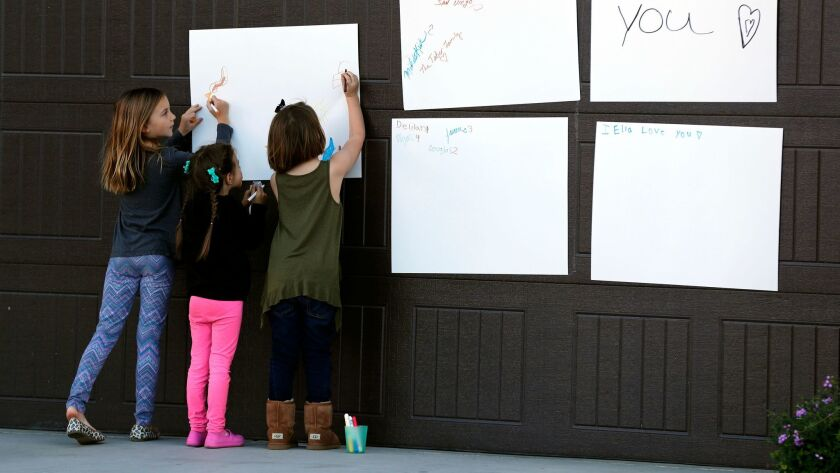 Children write notes of support on a poster in their Perris neighborhood for the 13 Turpin siblings, whose parents have been charged with torturing them.