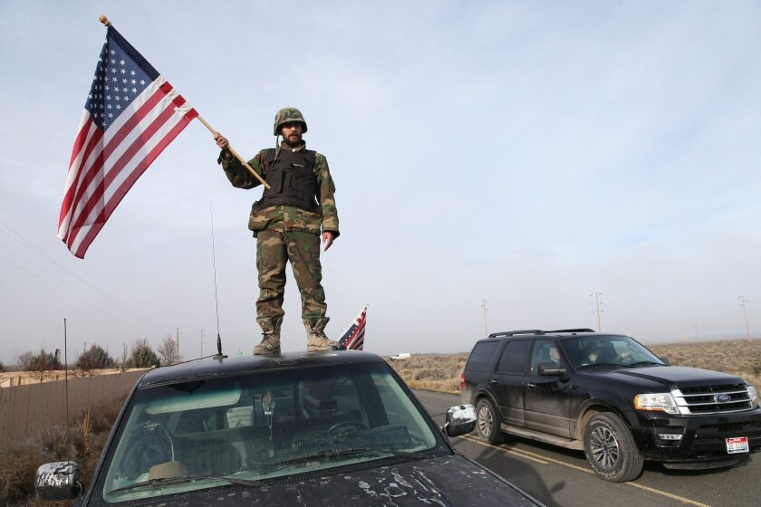 A man wave American flag from atop a car at the Narrows roadblock, Thursday, Feb. 11, 2016, near Burns, Ore. The last four occupiers of a Malheur National Wildlife Refuge in eastern Oregon surrendered Thursday. The holdouts were the last remnants of a larger group that seized the wildlife refuge ne