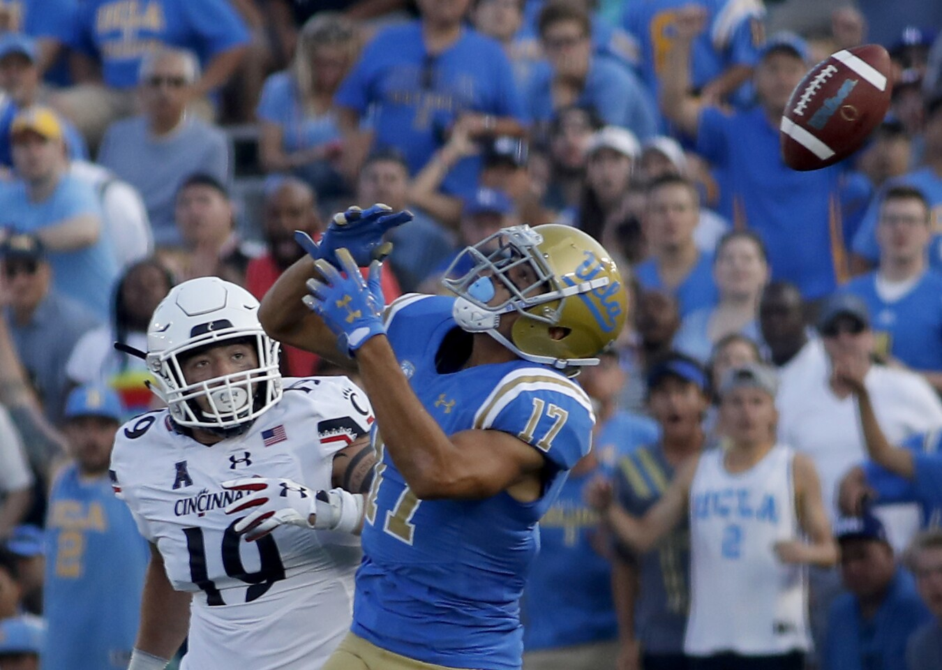 UCLA wide receiver Christian Pabico can't find the handle on a pass as Cincinnati's Ethan Tucky defends in the third quarter at the Rose Bowl in Pasadena on Saturday.