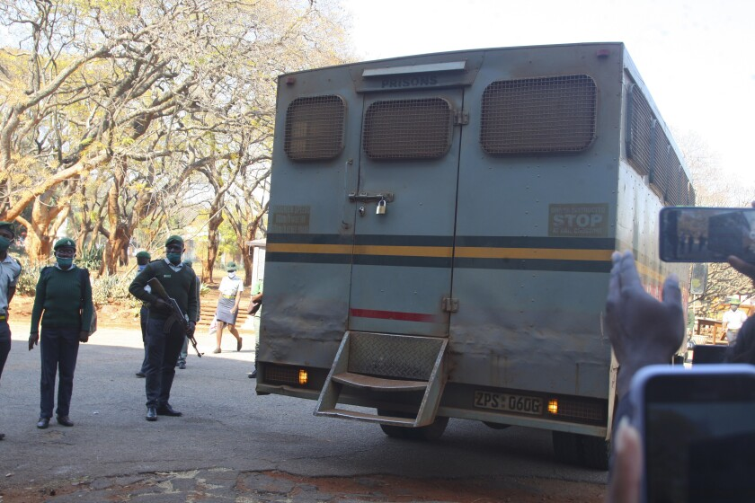 """An armed prison guard stands by the truck carrying Zimbabwean journalist Hopwell Chin'ono upon his arrival at the magistrates court, in Harare, Wednesday, Aug. 12, 2020. Lawyers for a jailed Zimbabwean journalist have asked a court to force prison authorities to stop the """"blatant and malicious stripping away"""" of his rights, including lack of access to appropriate food and warm clothing. (AP Photo/Tsvangirayi Mukwazhi)"""