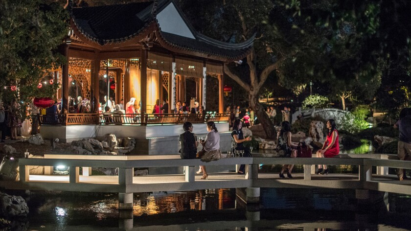 Attendees chat and eat in the Chinese Garden at the Huntington Library, Art Collections and Botanical Gardens during its annual Harvest Moon Celebration in 2014. The festival will be Sept. 27 this year.