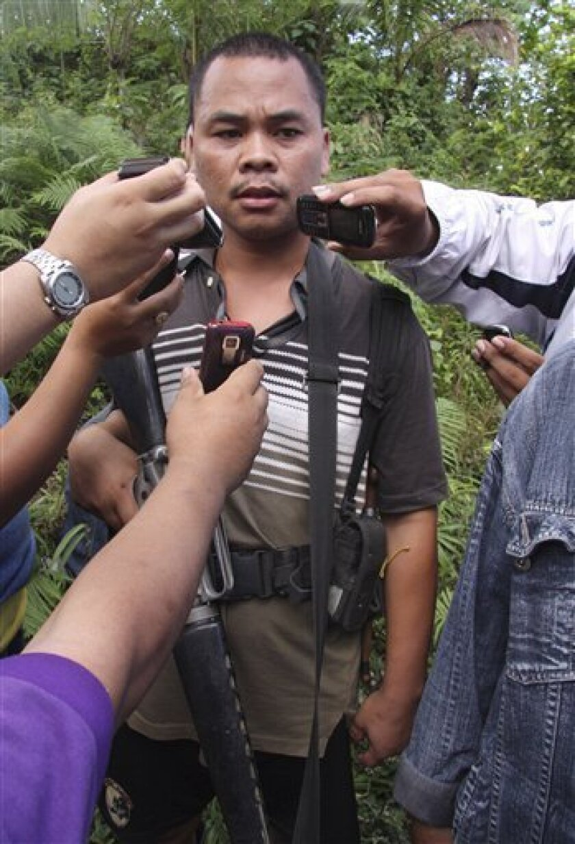 """Joebert """"Ondo"""" Perez, a Government-armed former militiaman, talks to the media at a remote village in Prosperidad township, Agusan del Sur province in southern Philippines Friday Dec. 11, 2009. Perez and his group took more than 70 people, including 17 school children hostage Thursday after police tried to serve summons for murder charges. Initially Perez released 18 hostages and released nine more Friday. (AP Photo)"""