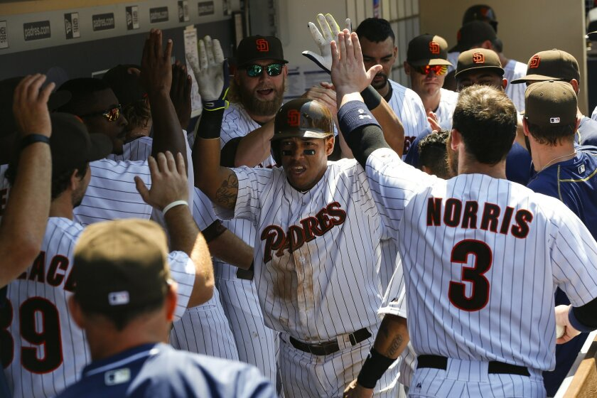 Padres Yangervis Solarte gets high fives after his solo home run against the Braves Wednesday afternoon at Petco Park.