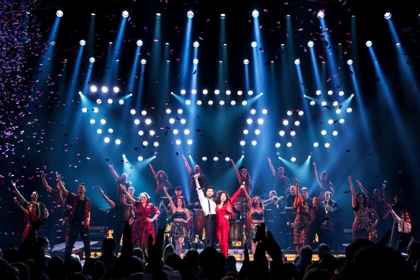 """Al centro, Mauricio Martínez y Christie Prades, quienes interpretan a Emilio Estefan y a Gloria Estefan, durante una escena culminante del musical """"On Your Feet!"""""""