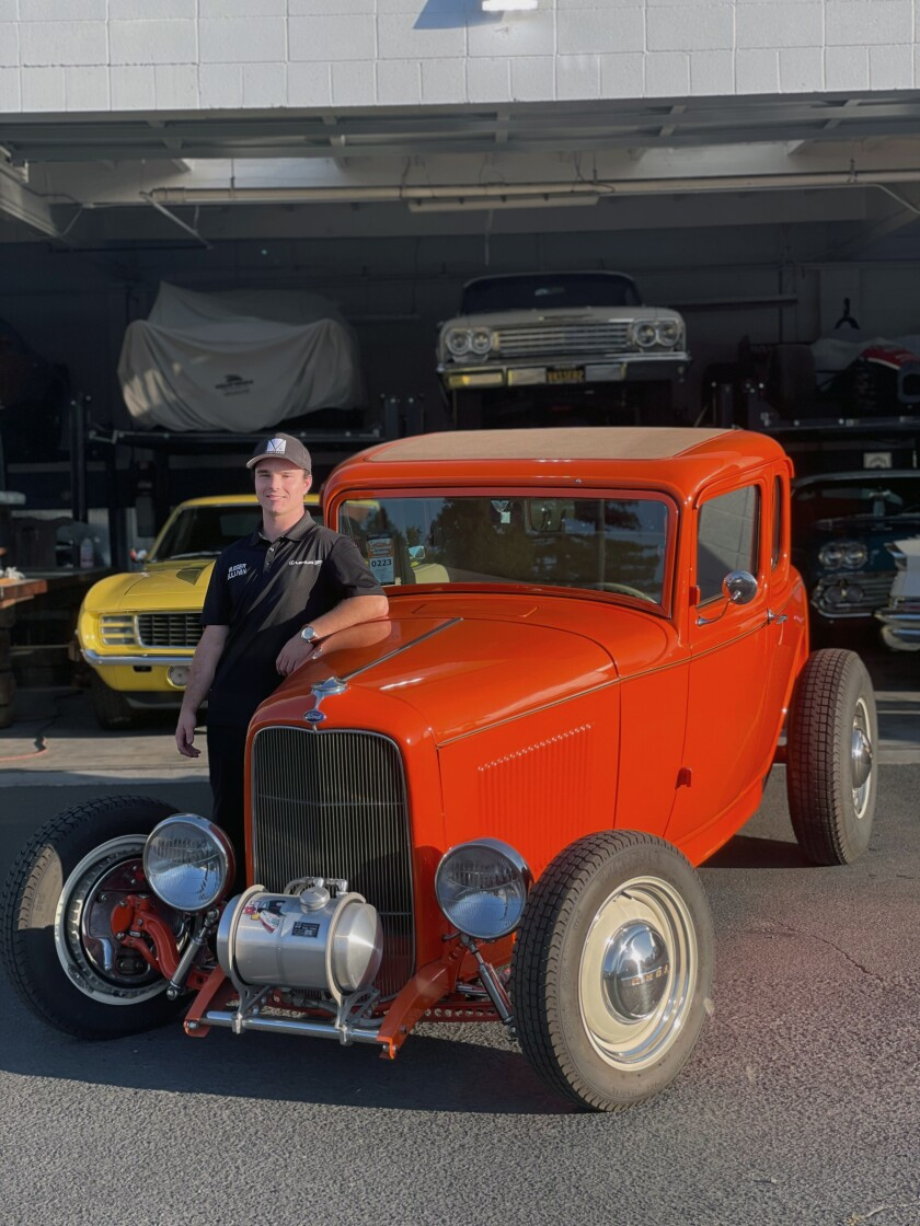 This August 2020 photo shows Cole Kleis standing next to a 1932 Ford Coup in front of a garage of old cars he's been restoring with his family in Napa, Calif. Automakers are facing a challenge with the newest generation of drivers — teens of today aren't in a hurry to get their first car let alone a drivers license. There are exceptions to the theory that teens don't care about cars, including 20-year-old Cole Kleis of Napa, California. Kleis attends Colorado State University at Pueblo, majoring in automotive industry management. He took his first job in a dealership at age 12 cleaning cars, sweeping floors and helping in the parts department. (AP Photo/Jenna Fryer)