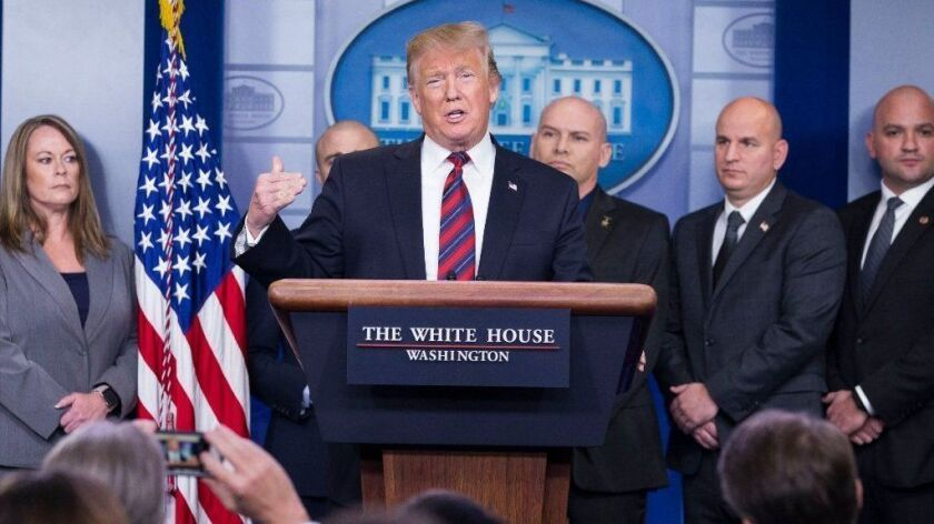 President Trump delivers a statement on border security and the ongoing partial shutdown of the federal government, with members of the National Border Patrol Council, in the White House briefing room.