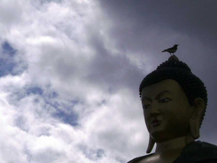 A Buddha statue in Tyva Republic sits on a hilltop overlooking visitors. A new study finds that people who believed in all-knowing, punitive gods with moral judgment were more likely to play fair in a pair of experimental games.
