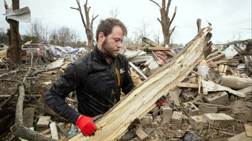 Steven Tirpak cleans debris from the remains of his two-story home in Taylorville, Ill., on Sunday. Tirpak and his infant were not home when the storm struck. The National Weather Service says multiple tornadoes touched down in central Illinois.