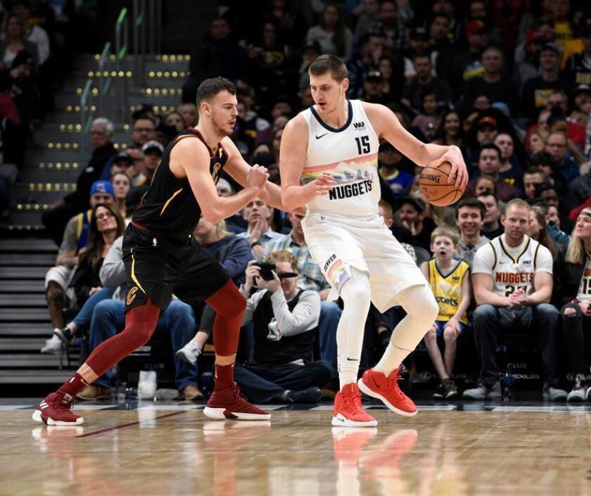 Nikola Jokic (d) de Denver Nuggets protege la pelota de la marca de Ante Zizic (i) de Cleveland Cavaliers durante el juego de la NBA. EFE/Archivo