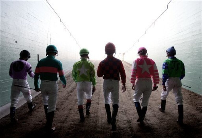 """In this image released by Animal Planet, Jockeys, from left, Alex Solis, Mike Smith, Jon Court, Aaron Gryder, Chantal Sutherland and Joe Talamo walk at the Santa Anita Race Track, Arcadia, Calif., on Sept. 23, 2008. """"Jockeys,"""" a 12-episode series taking viewers behind the scenes in the backstabbing, big-money, dangerous world of horse racing, debuts Friday, Feb. 6, 2009, on Animal Planet. (AP Photo/Animal Planet, Donald Miralle)"""