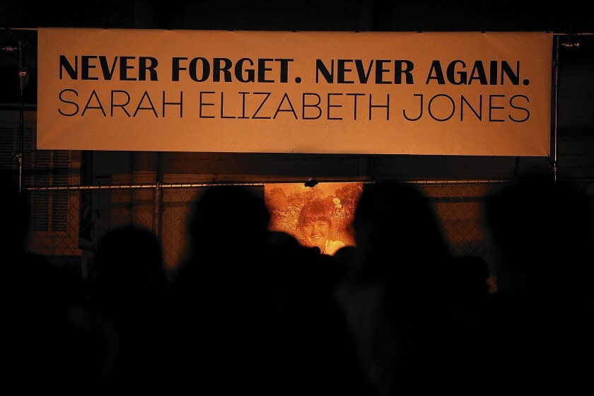 """A banner above a photo of Sarah Jones reads, """"Never forget. Never again."""""""