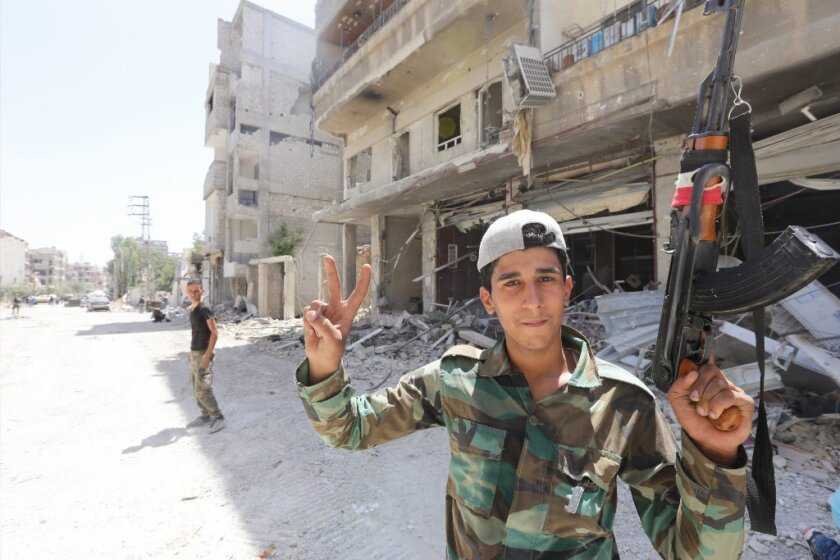A Syrian soldier greets journalists in a town near Damascus on Friday.