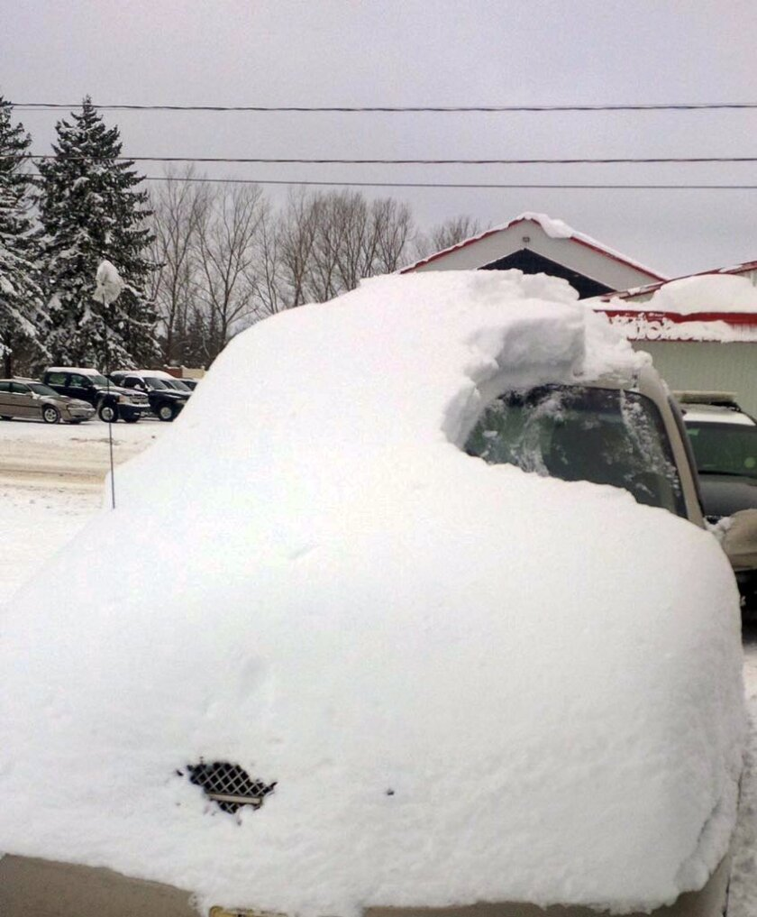 This Tuesday, Jan. 19, 2016 photo provided by the Ontario Provincial Police shows a snow covered vehicle in Brussels, Ontario. An 80-year-old man has been charged after driving the car that was almost completely covered in snow with only the driver's side windshield visible. (Sgt. Russell Nesbitt/Ontario Provincial Police via AP)