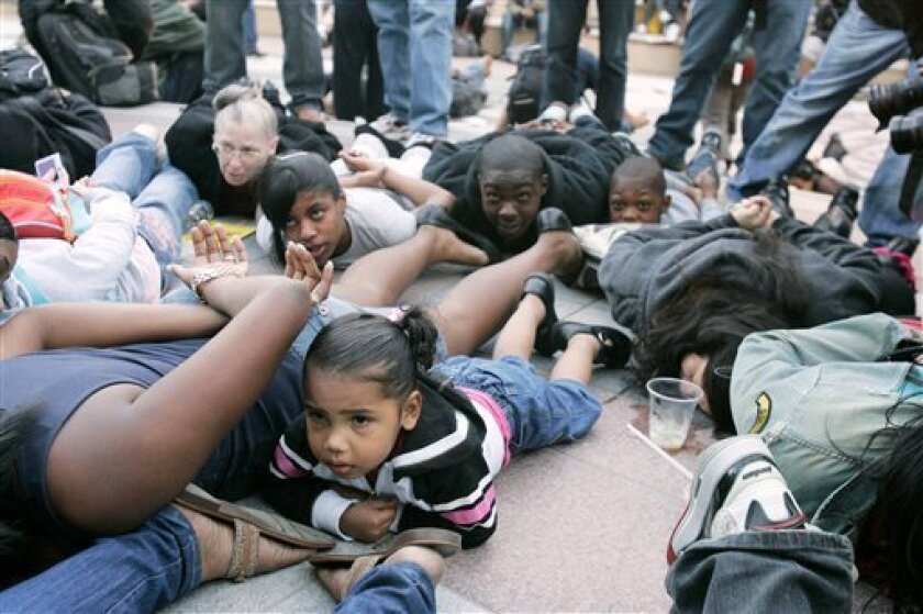 A young girls join protesters in a mock arrest pose during a protest against the shooting death of Oscar Grant  in Oakland, Calif. Wednesday, Jan. 14, 2009.    A former transit police officer has been charged with murder for the fatal shooting of an unarmed and allegedly restrained black man in a r