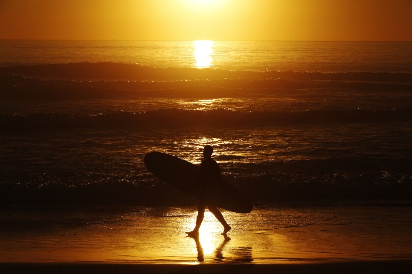 A man carries a surfboard at sunset on the beach