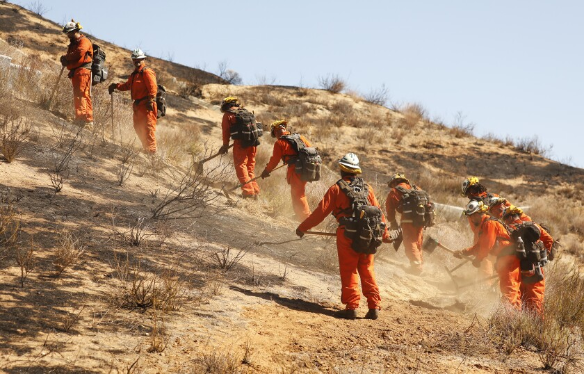 Firefighters clear brush on a hillside to establish perimeter control for containment of the North fire near Castaic.