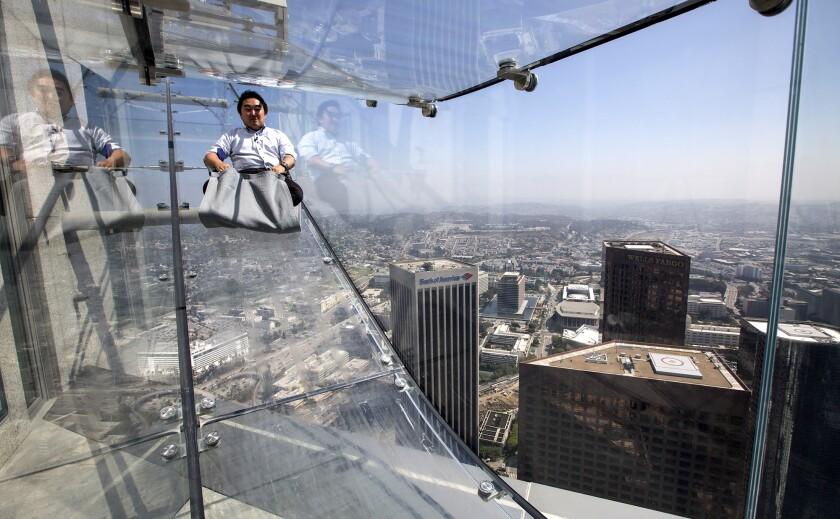Man slides glass slide over downtown Los Angeles