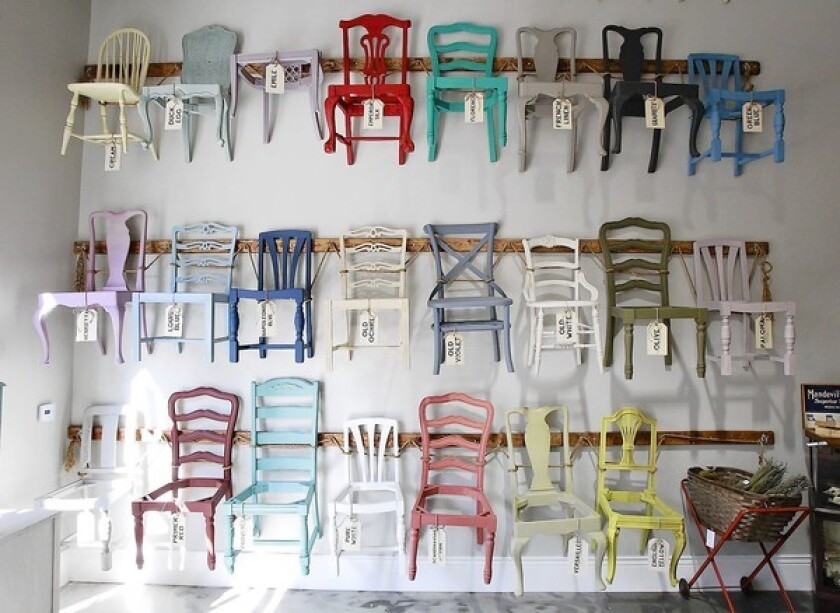 Wooden chairs painted in various chalk paint colors hang on the walls of Peinture in SoCo Collection in Costa Mesa.