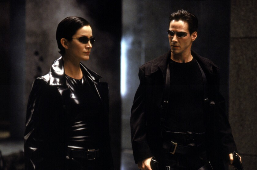 """Carrie-Anne Moss as Trinity, left, and Keanu Reeves as Neo in Warner Bros' futuristic action-thriller """"The Matrix."""""""