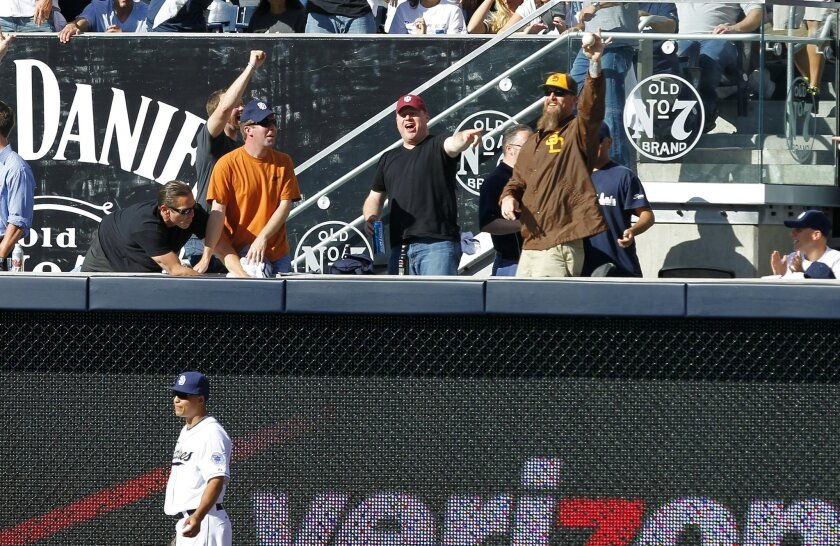 A fan catches a home run by Dodgers Juan Uribe at the shortened right field fences above Padres Will Venable.