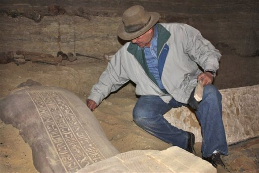 In this photo released Monday, Feb. 9, 2009 by Egypt's Supreme Council of Antiquities, Egypt's top archaeologist Zahi Hawass examines a newly-discovered Egyptian mummy in a sarcophagus in a tomb at Saqqara, south of Cairo, in Egypt, Sunday, Feb. 8, 2009. Egyptian archaeologists say they have discovered 30 mummies inside a 2,600-year-old tomb, discovered at an even more ancient site dating back to the 4,300-year-old 6th Dynasty, in the latest round of excavations at the vast necropolis of Saqqara south of Cairo. (AP Photo/Supreme Council of Antiquities)