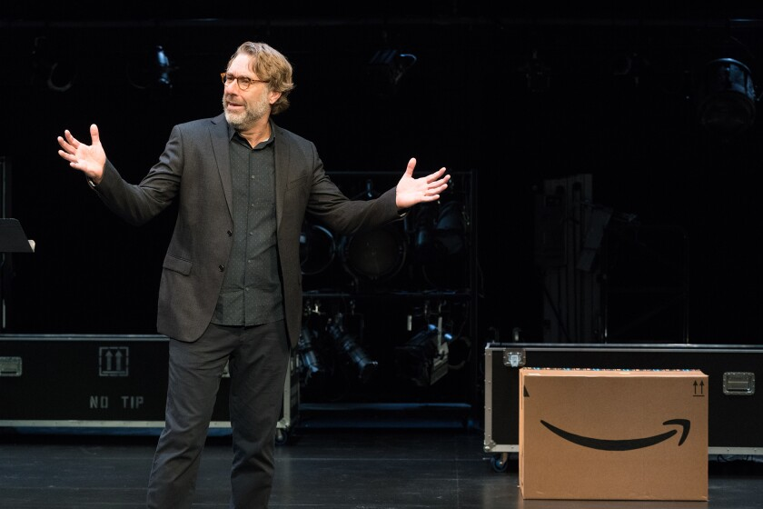 A man on a stage, dressed in a dark suit, gestures.