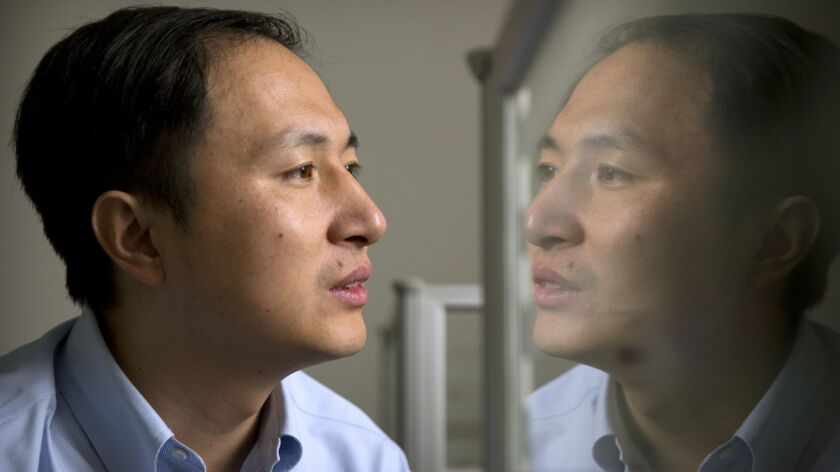 In this Oct. 10, 2018 photo, He Jiankui is reflected in a glass panel as he works at a computer at a