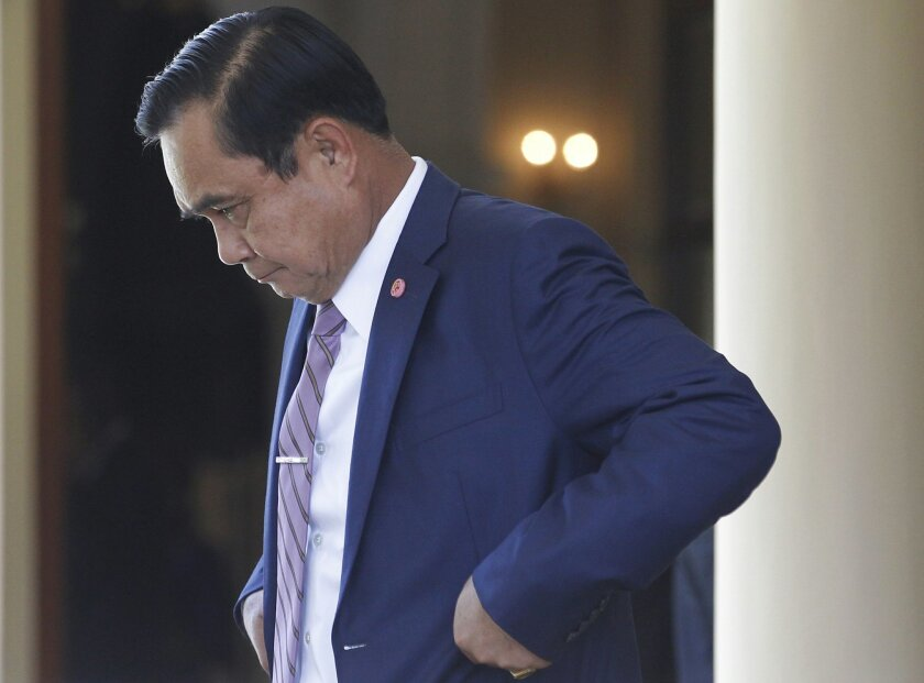 """Thailand's Prime Minister Prayuth Chan-ocha, center, leaves a meeting at Government House in Bangkok, Thailand, Thursday, April 2, 2015. Thailand's junta lifted martial law, which was imposed in the run-up to their May 22, 2014, coup -- but then quickly replaced it with another set of draconian laws innocuously called """"Article 44."""" But make no mistake -- 10 months after staging the coup, a military junta is still ruling Thailand, essentially with absolute power. (AP Photo/Sakchai Lalit)"""