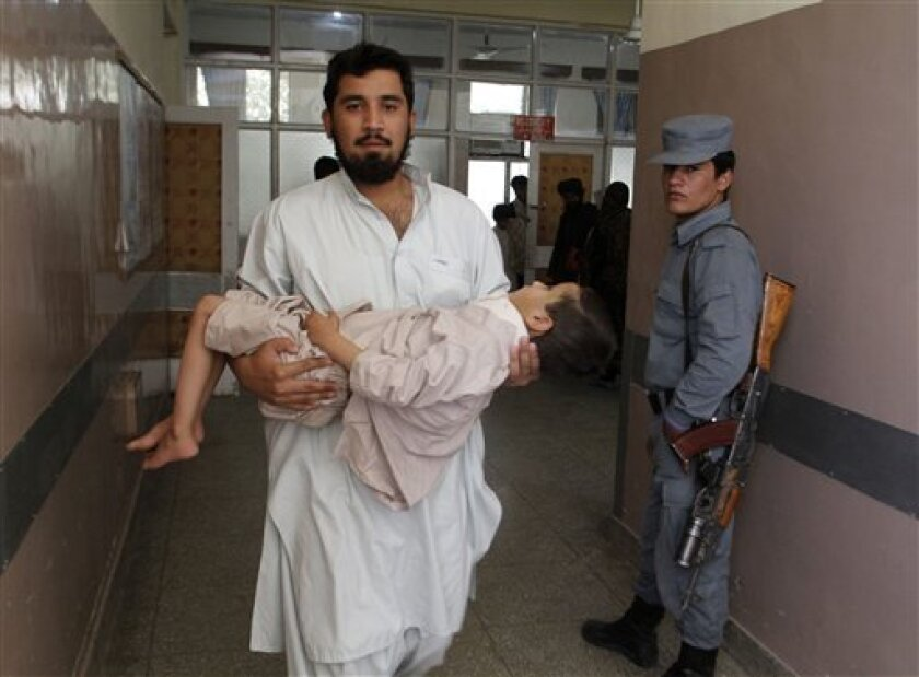 An Afghan doctor carries a boy for treatment at a hospital after a suicide bomb explosion in Kandahar province, southwest of Kabul, Afghanistan, Saturday, Aug. 31, 2013. A suicide bomber detonated his explosives near a police checkpoint and a bank in southern Afghanistan on Saturday, killing severa