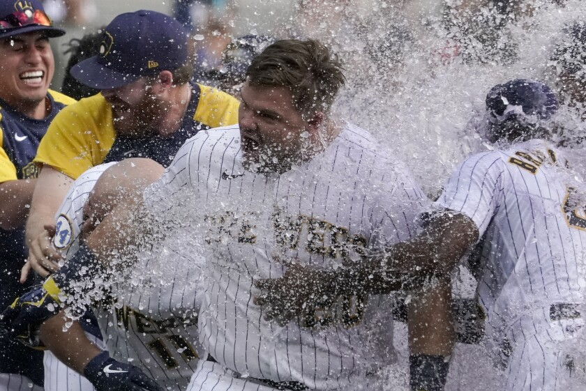 Milwaukee Brewers' Daniel Vogelbach is congratulated by teammates after hitting a walk-off grand slam during the ninth inning of a baseball game against the St. Louis Cardinals Sunday, Sept. 5, 2021, in Milwaukee. The Brewers won 6-5. (AP Photo/Morry Gash)
