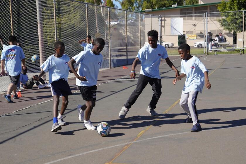 Los niños del programa STAR / PAL juegan un partido de futsal en el parque Colina del Sol