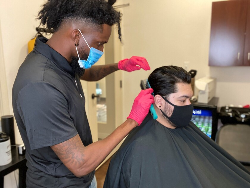 Alexander Shelton cuts a client's hair at Gallery of Grooming in La Jolla.