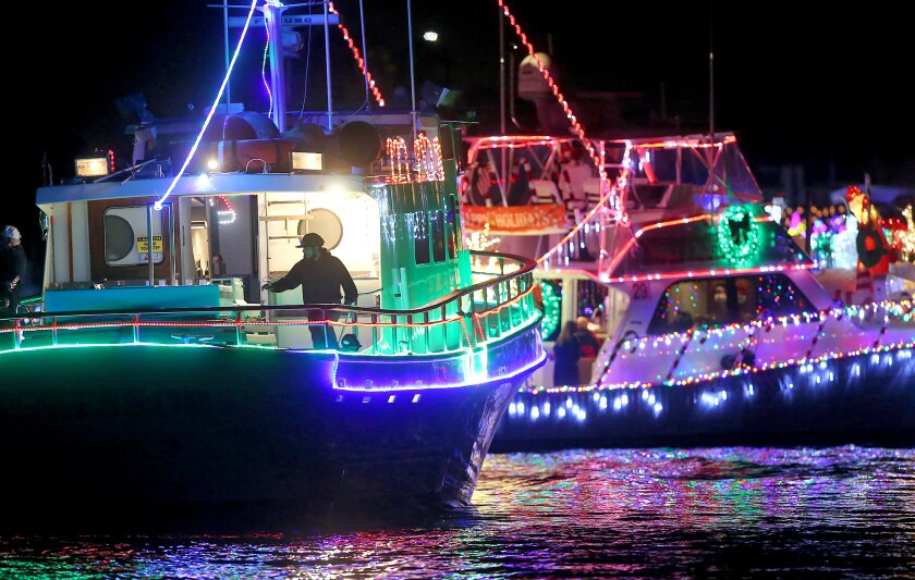 A fishing vessel and a crewman stay in line along the route during the 2019 Newport Beach Christmas Boat Parade.