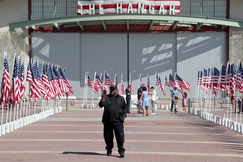 Milo Levell, holds up his smartphone as he records the display of American flags during a 20-year 9/11 remembrance events.