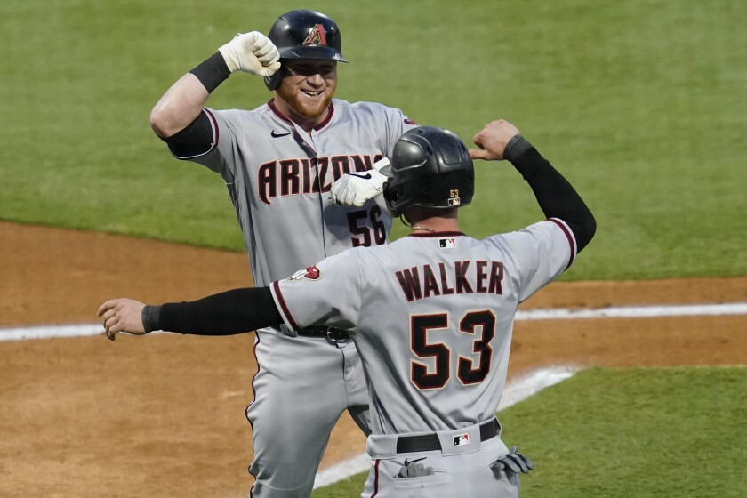 Arizona Diamondbacks' Kole Calhoun, left, celebrates a two-run home run with Christian Walker during the first inning of the team's baseball game against the Los Angeles Angels on Tuesday, Sept. 15, 2020, in Anaheim, Calif. (AP Photo/Ashley Landis)