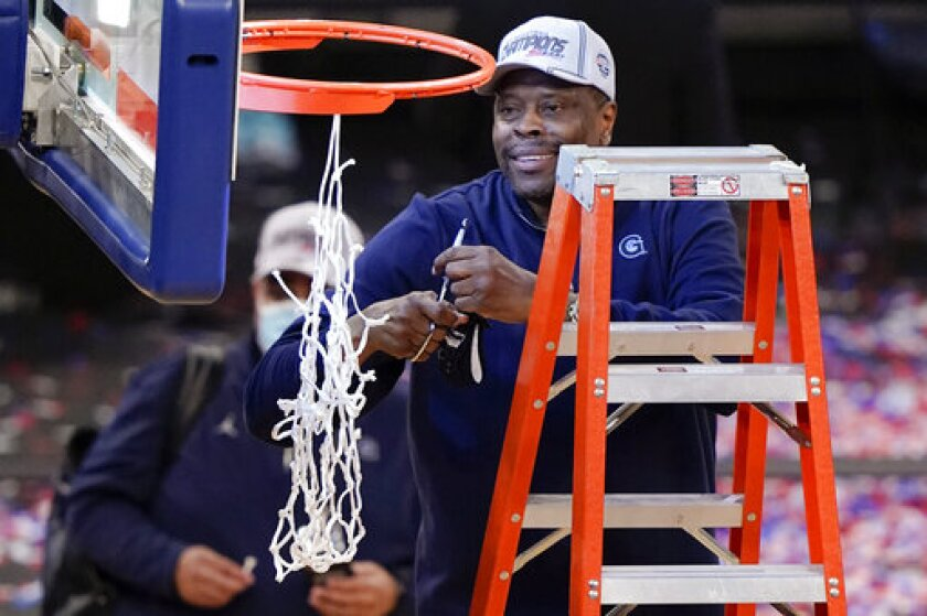 Georgetown coach Patrick Ewing cuts down the net after winning the Big East tournament in March.