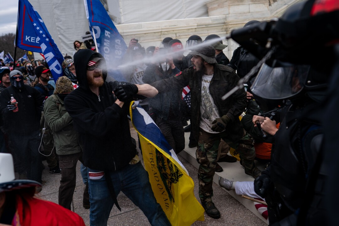 A man is sprayed in the face as protesters clash with police