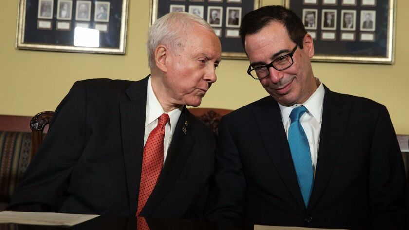 Treasury Secretary Steven T. Mnuchin, right, listens to Senate Finance Committee Chairman Orrin Hatch (R-Utah) during a meeting about tax legislation in the U.S. Capitol on Thursday.