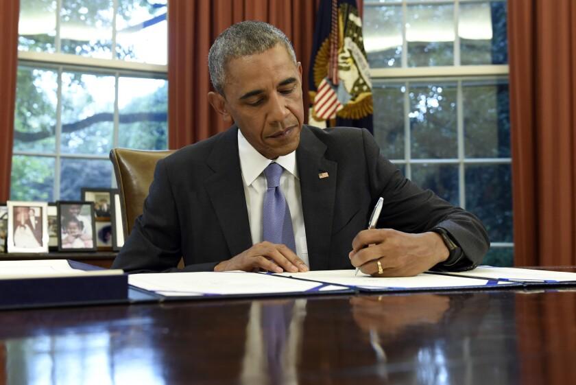 El presidente Barack Obama firma la Ley FOIA Improvement en la Oficina Oval de la Casa Blanca el jueves 30 de junio de 2016 en Washington. El mandatario también firmó la ley para supervición, administración y estabilidad económica de Puerto Rico. (AP Foto/Susan Walsh)
