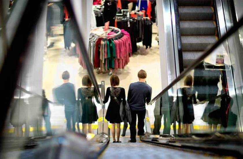 A couple descend an escalator while shopping at an H&M; store in Atlanta. As of Tuesday working Americans saw a tax on their paychecks rise to 6.2% from 4.2% last year. Economists estimate that this could strip $115 billion in disposable income from the economy this year.