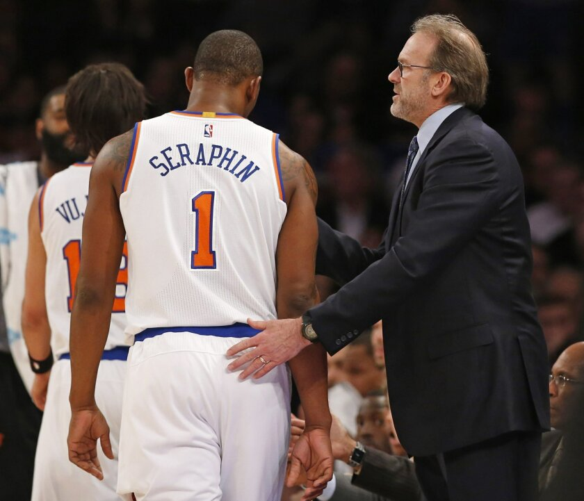New York Knicks interim head coach Kurt Rambis, in his first game coaching the Knicks after replacing fired coach Derek Fisher, pats New York Knicks center Kevin Seraphin (1) on the back during a timeout in the first half of an NBA basketball game against the Washington Wizards at Madison Square Ga