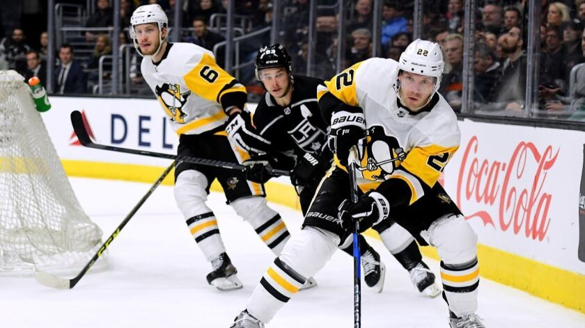 Pittsburgh Penguins' Matt Hunwick (22) clears the puck as he is chased by Kings' Dustin Brown and teammate Jamie Oleksiak (6) during the second period at Staples Center on Thursday.