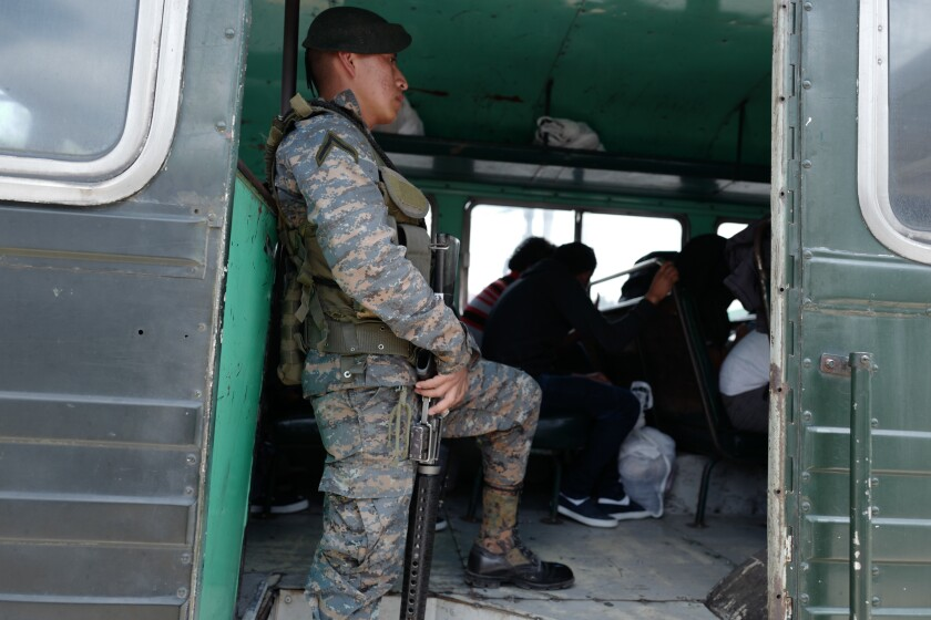 A soldier watches over a bus carrying U.S. detainees upon their return to Guatemala.
